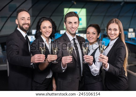 Portrait of a young businessman with business team in modern conference hall with glasses of champagne. - stock photo