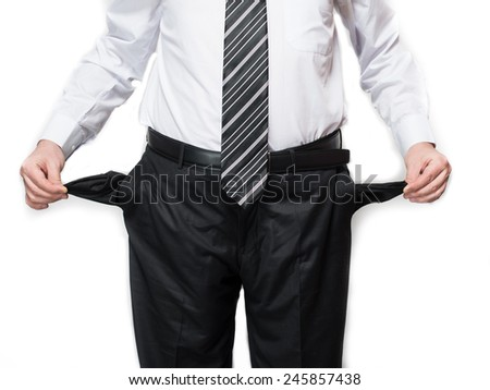 portrait of a young businessman with empty pockets on a gray background