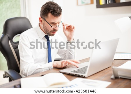 Portrait of a young businessman with eye fatigue looking over his glasses while working on a laptop computer in an office