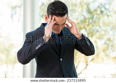 Portrait of a young businessman with his hands on his temples stressing out - stock photo