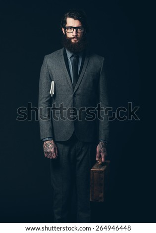 Portrait of a Young Businessman with long Goatee Beard, Standing in Formal Suit with Eyeglasses, Holding a Briefcase While Looking at the Camera. Isolated on Black Background. - stock photo