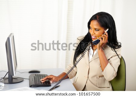 Portrait of a young businesswoman conversing on phone and looking to the monitor screen
