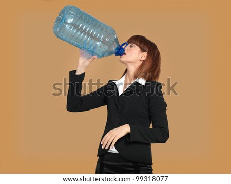 portrait of a young businesswoman, drinking water from a big bottle, on beige background