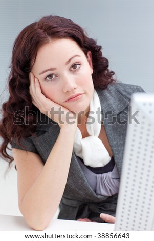 Portrait of a young businesswoman in front of a computer getting bored - stock photo