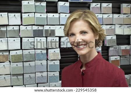 Portrait of a young businesswoman in front of a wall of fabric samples - stock photo
