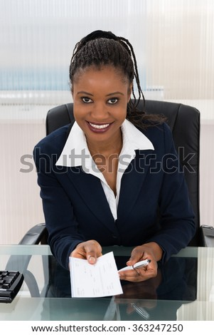 Portrait Of A Young Businesswoman Offering Cheque - stock photo