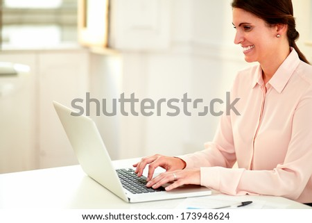 Portrait of a young businesswoman on pink blouse working with her laptop while smiling and sitting on office desk - copyspace - stock photo