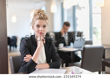 Portrait of a young businesswoman, sitting and writing at a table, a businessman blurred in the background - stock photo