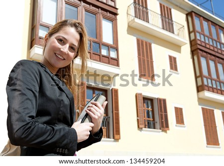 Portrait of a young businesswoman standing near classic office buildings in a city, carrying a digital tablet pad and a folder while smiling at the camera. - stock photo