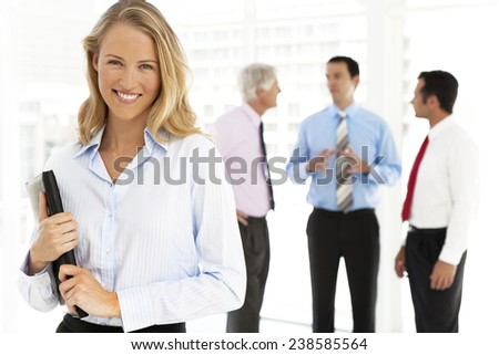 Portrait of a young businesswoman standing on foreground with business partners talking on background. Focus on her. - stock photo