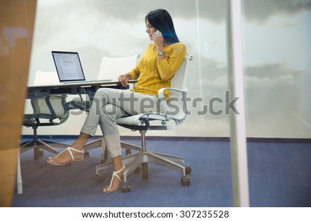 Portrait of a young businesswoman talking on the phone at her workplace in office - stock photo