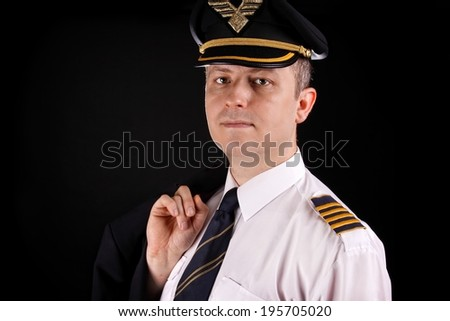 Portrait of a young captain in uniform on a black background - stock photo