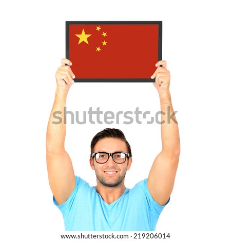 Portrait of a young casual man holding up board with National flag of  - stock photo