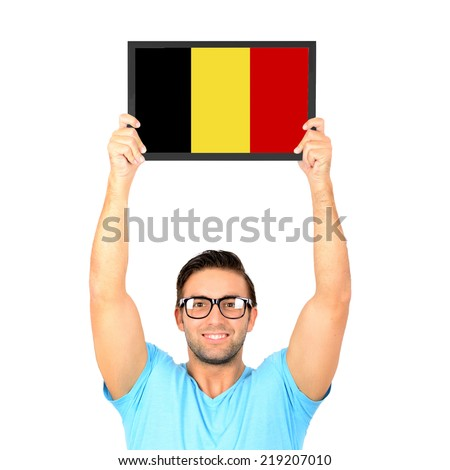 Portrait of a young casual man holding up board with National flag of Belgium - stock photo