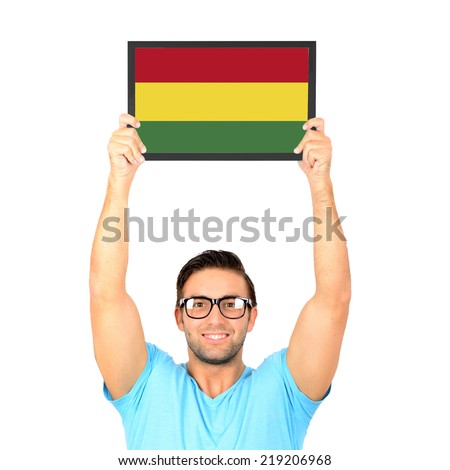 Portrait of a young casual man holding up board with National flag of Bolivia - stock photo