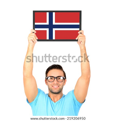 Portrait of a young casual man holding up board with National flag of Norway - stock photo