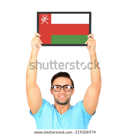Portrait of a young casual man holding up board with National flag of Oman - stock photo