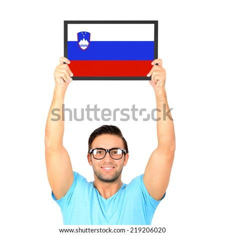 Portrait of a young casual man holding up board with National flag of Slovenia - stock photo