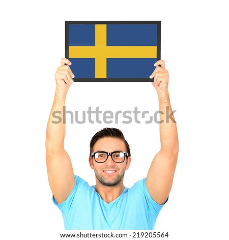 Portrait of a young casual man holding up board with National flag of Sweden - stock photo