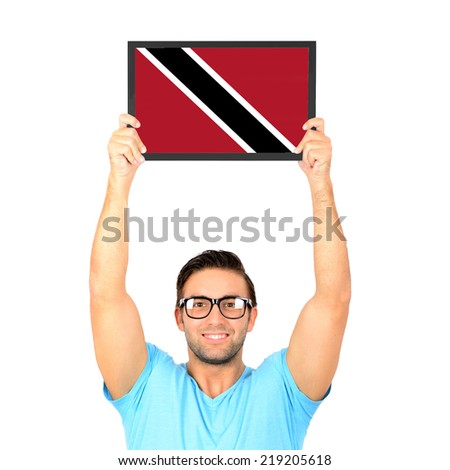 Portrait of a young casual man holding up board with National flag of Trinidad and Tobago - stock photo