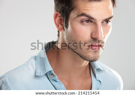 Portrait of a young casual man in blue shirt, on gray background - stock photo