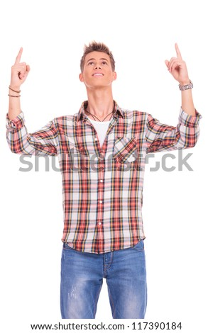 portrait of a young casual man looking and pointing with both hands upward - stock photo