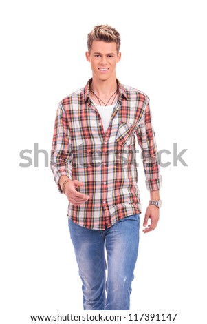 portrait of a young casual man walking toward the camera and smiling, on white background