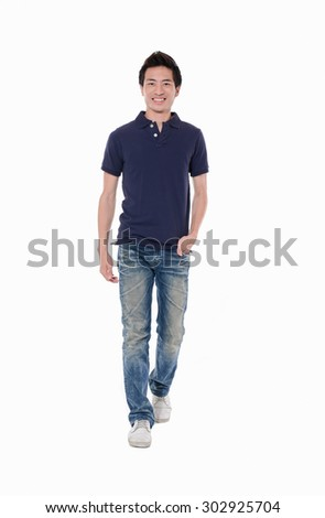 portrait of a young casual young man walking in studio - stock photo