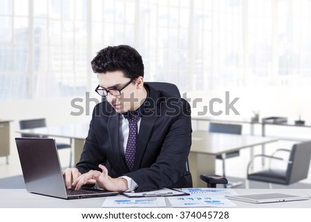 Portrait of a young caucasian entrepreneur looks busy while typing on the laptop with document at desk, shot in the office