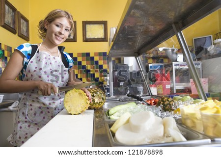 Portrait of a young Caucasian female cutting pineapple at counter of diner - stock photo