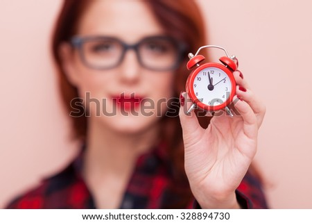 Portrait of a young caucasian girl in glasses with Clock on pink background.