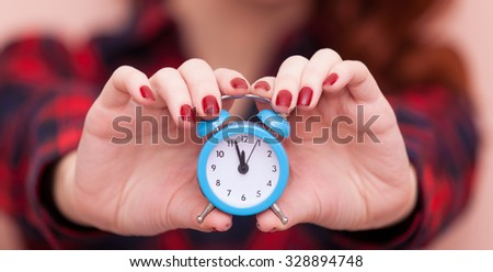 Portrait of a young caucasian girl with Clock on pink background.