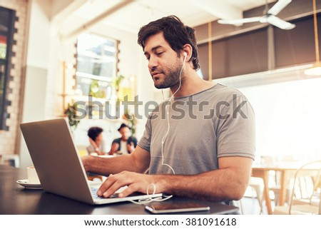 Portrait of a young caucasian man with earphones using laptop at a cafe. Man with beard working on laptop computer at a coffee shop. - stock photo