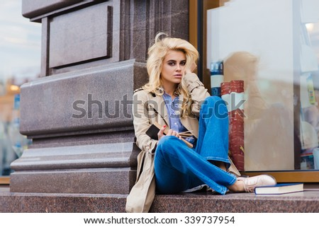 Portrait of a young charming blonde model posing while sitting with open book outdoors on a store sill, beautiful woman student with perfect look reading textbook before start lectures in University  - stock photo