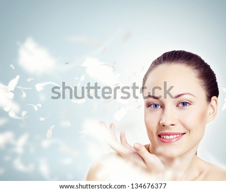Portrait of a young charming girl on a background of soaring light feathers