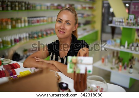 Portrait of a young charming successful woman entrepreneur posing while standing in her cosmetic shop interior, beautiful female professional consultant looking at you during work day in drugstore  - stock photo