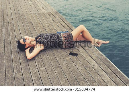 Portrait of a young charming woman enjoying recreation time during her summer weekend, female tourist relaxing after telephone conversation while lying on a river jetty with copy space area - stock photo