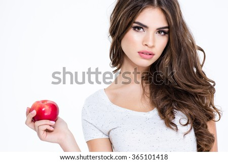 Portrait of a young charming woman holding apple isolated on a white background and looking at camera - stock photo