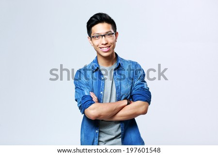 Portrait of a young cheerful asian man with arms folded on gray background - stock photo