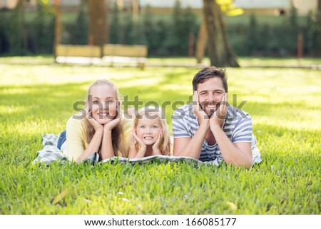 Portrait of a young cheerful family lying on the grass and posing at camera