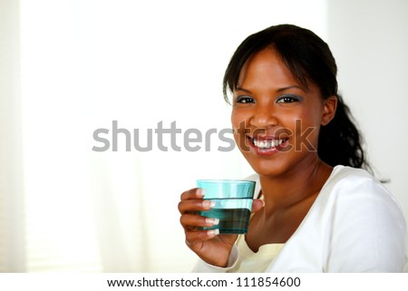 Portrait of a young cheerful woman smiling and drinking healthy cool water while looking to you. With copyspace. - stock photo