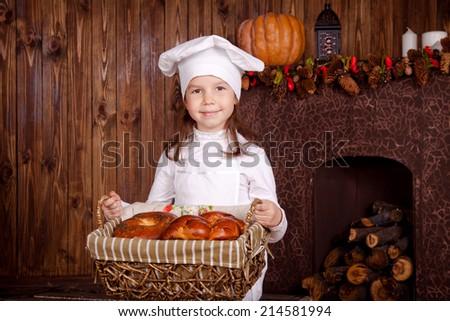 Portrait of a young chef with a basket of pastries - stock photo