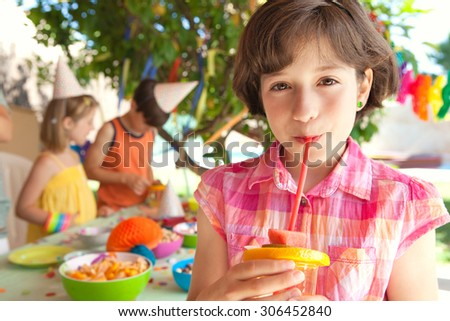 Portrait of a young child girl smiling, holding and drinking fruit juice with a straw at a home garden birthday party, outdoors lifestyle. Kids celebrating at colorful party table in a house exterior. - stock photo