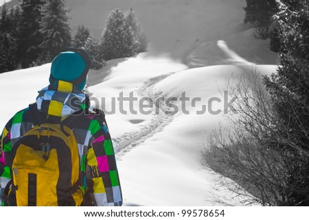 Portrait of a young climber walking on a thin path through the great drifts of snow. In the background black and white landscape.