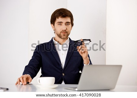 Portrait of a young confident businessman in suit sitting at office at the desk looking at camera. - stock photo