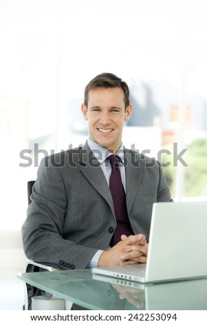 Portrait of a young confident businessman sitting at workplace