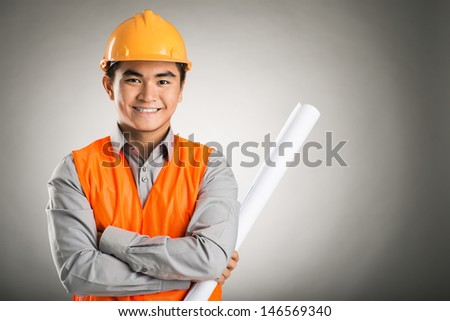 Portrait of a young confident engineer isolated on grey - stock photo