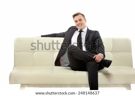 Portrait of a young confident smiling man with a suit sitting on the couch and looking at camera. Successful human context.