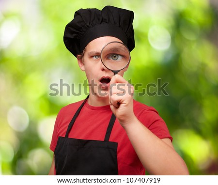 portrait of a young cook man looking through a magnifying glass against a nature background