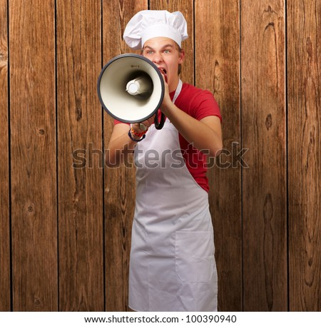portrait of a young cook man screaming with a megaphone against a wooden wall - stock photo